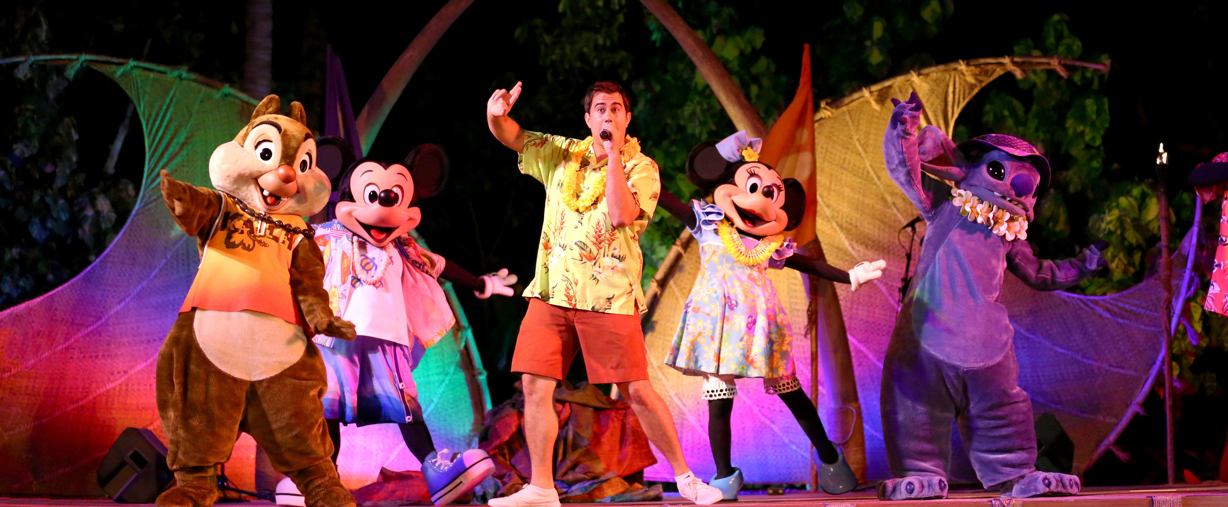 A Cast Member sings and dances onstage with Dale, Mickey, Minnie and Stitch