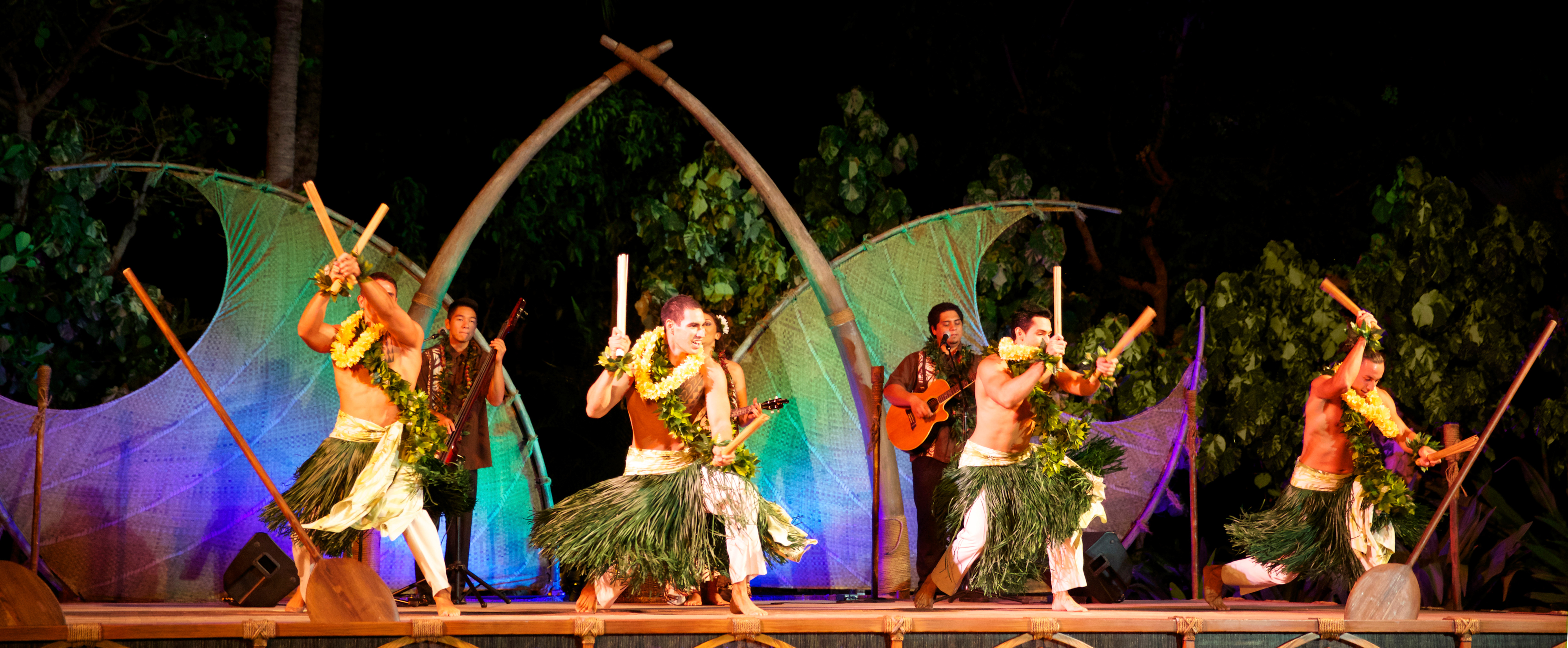 Four men in grass skirts perform onstage with kālaʻau rhythm sticks while musicians play behind them