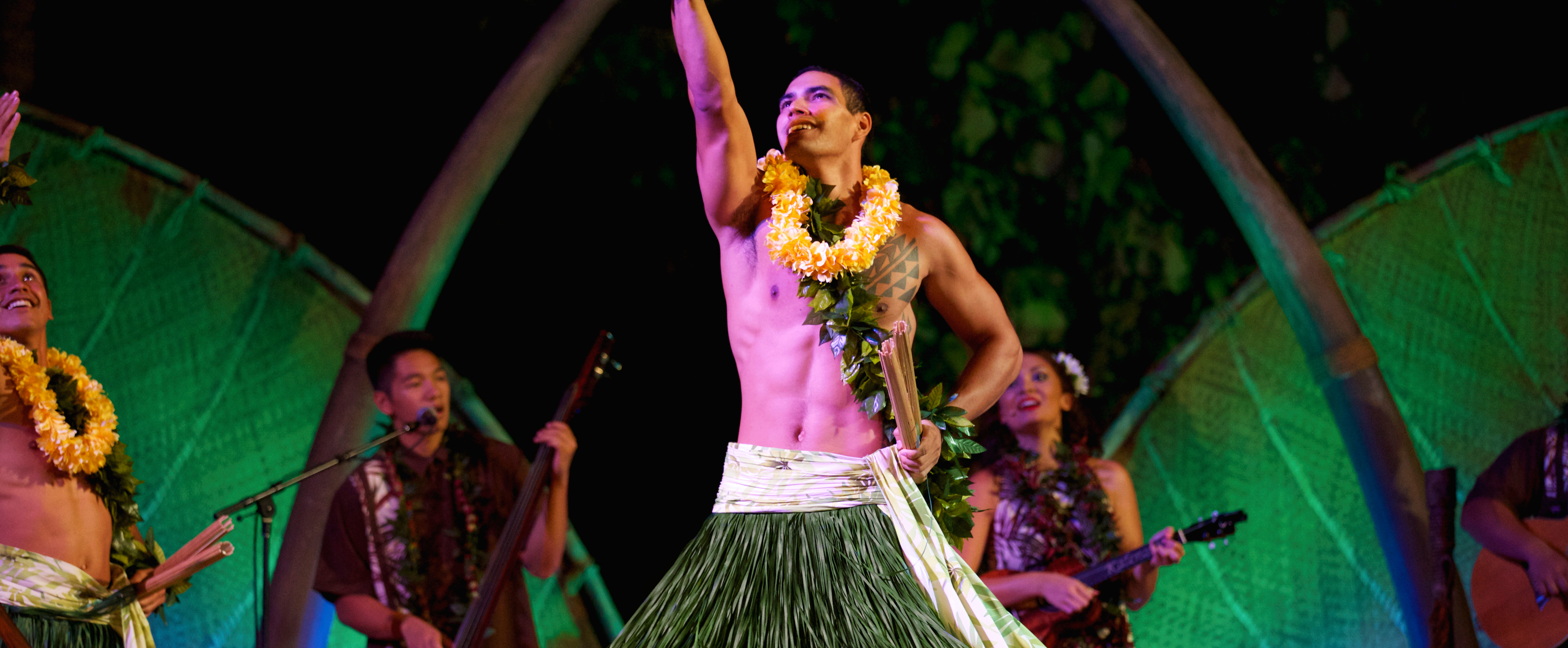 Two smiling male performers with pūʻili split bamboo sticks reach skyward as musicians play behind them