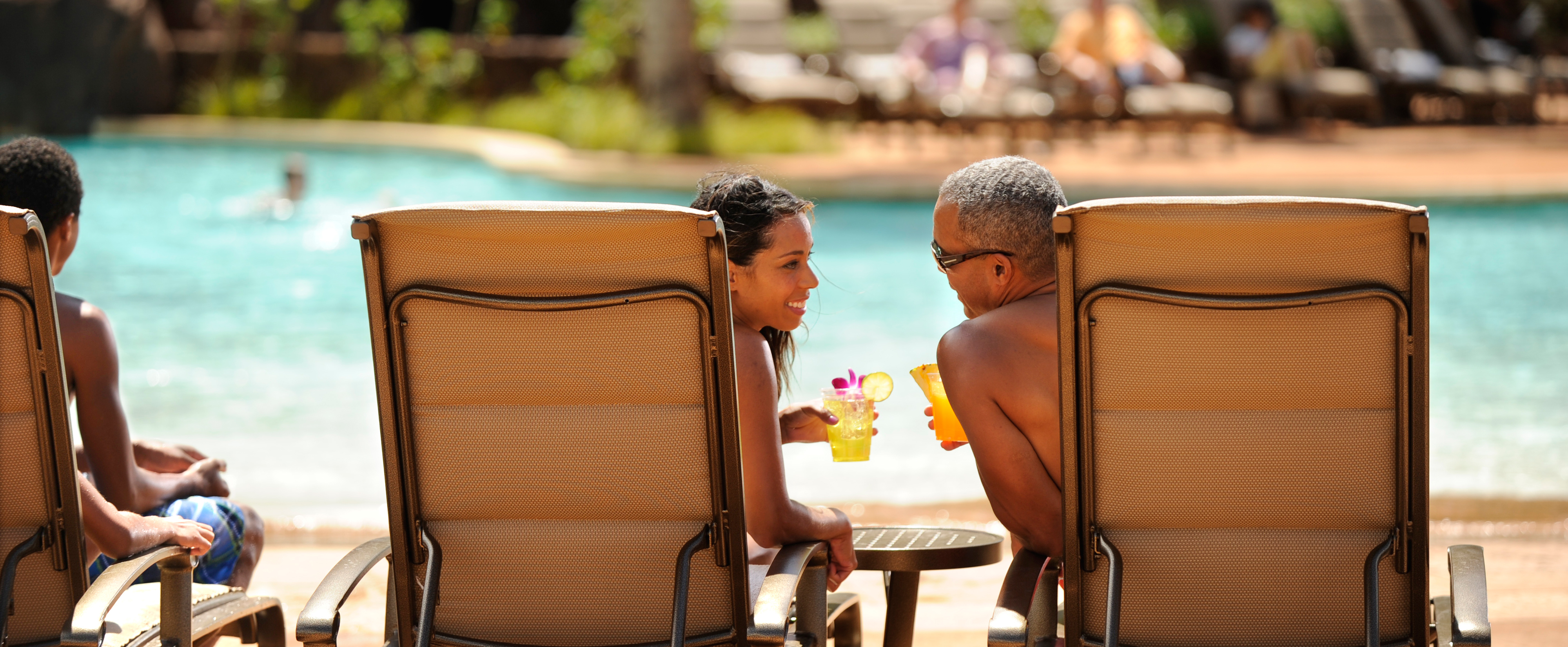 A woman and man sitting in lounge chairs lean in to talk to one another while holding drinks