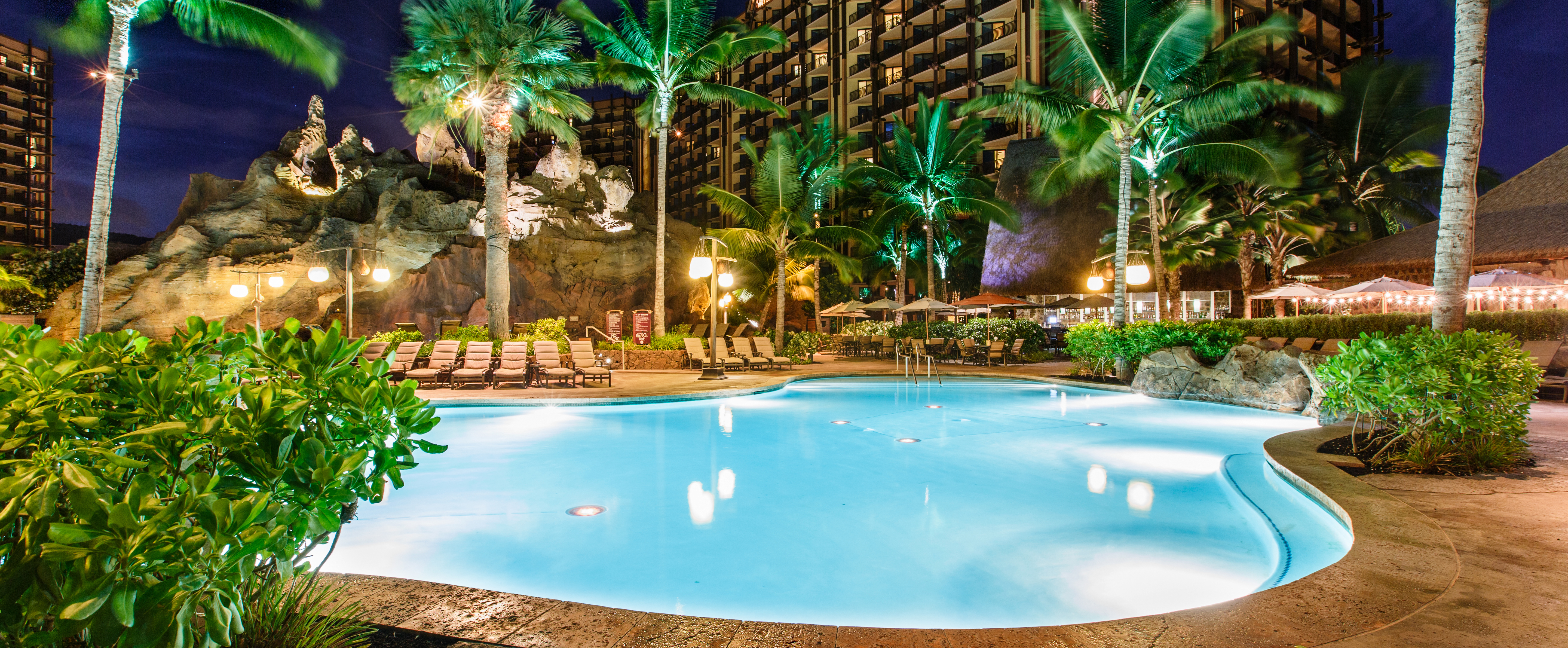 Waikolohe Pool lit up at night, surrounded by lounge chairs, palm trees and shrubs