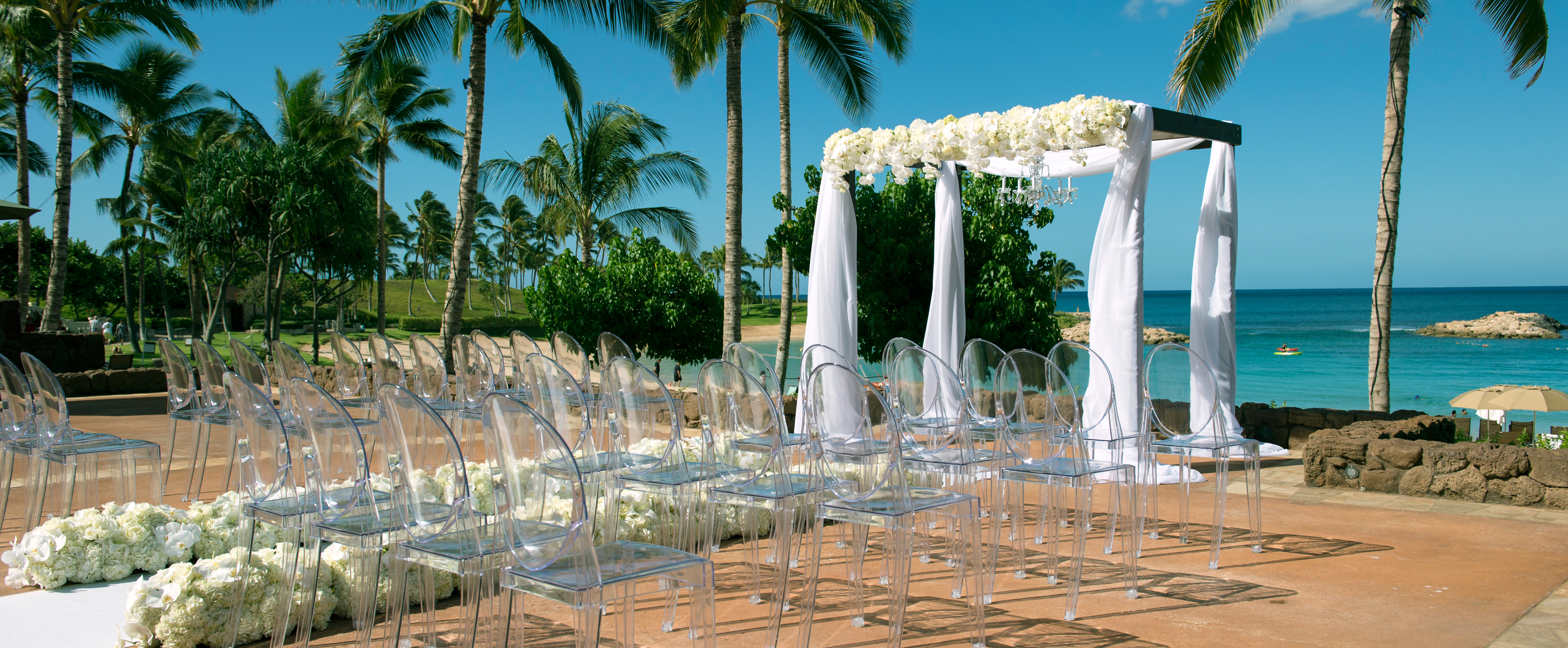 Rows of transparent chairs line an aisle leading to a seaside altar draped in white fabric and flowers