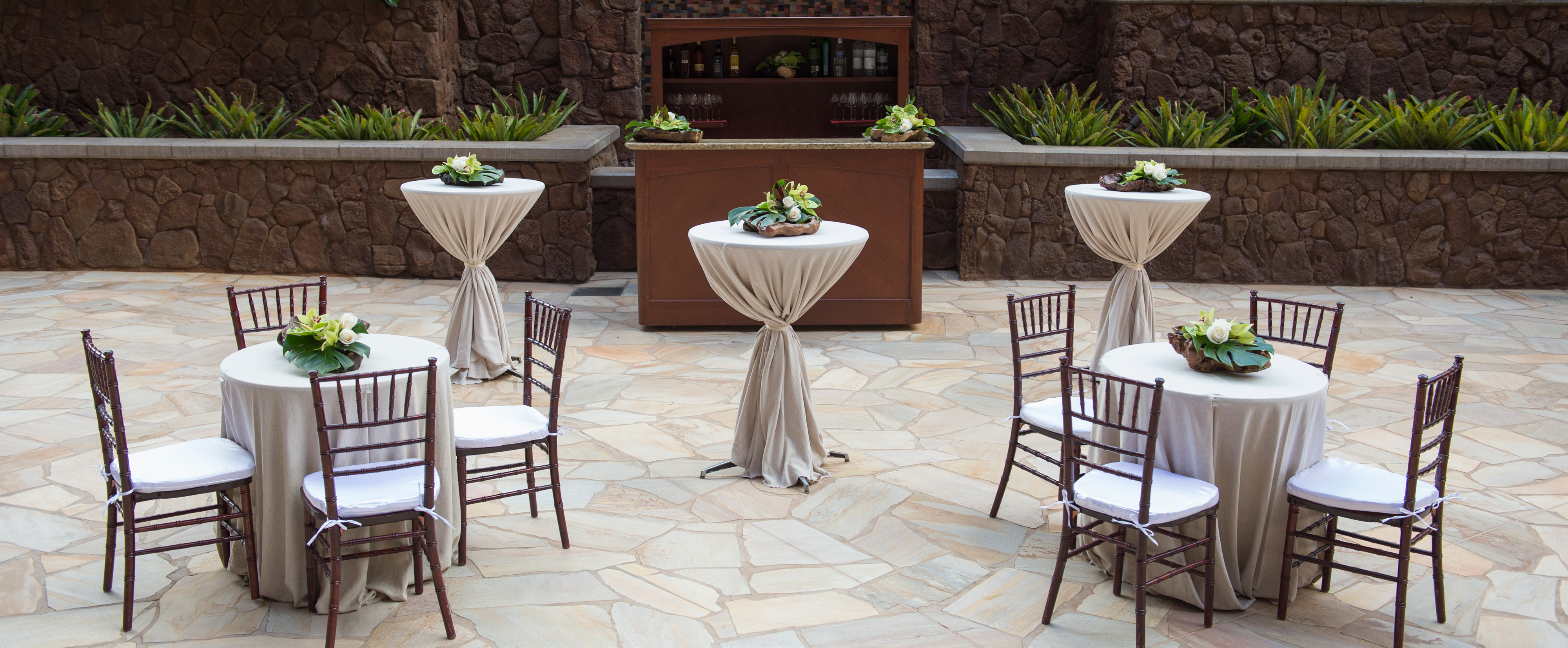 A courtyard setting with 2 tables for 4 and 3 fabric-draped bar tables, all with tropical centerpieces