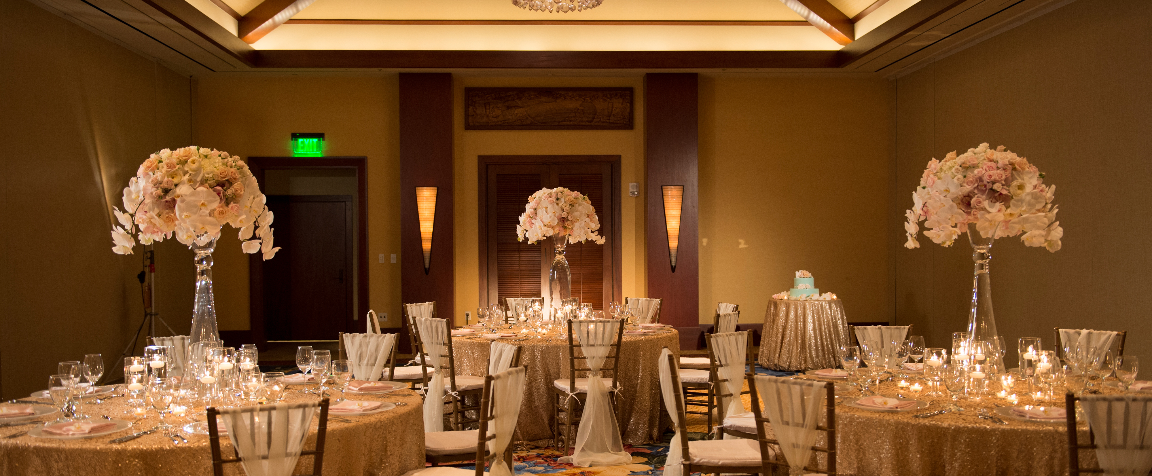 Three tables with tall floral centerpieces, floating candles and glass stemware in a banquet room