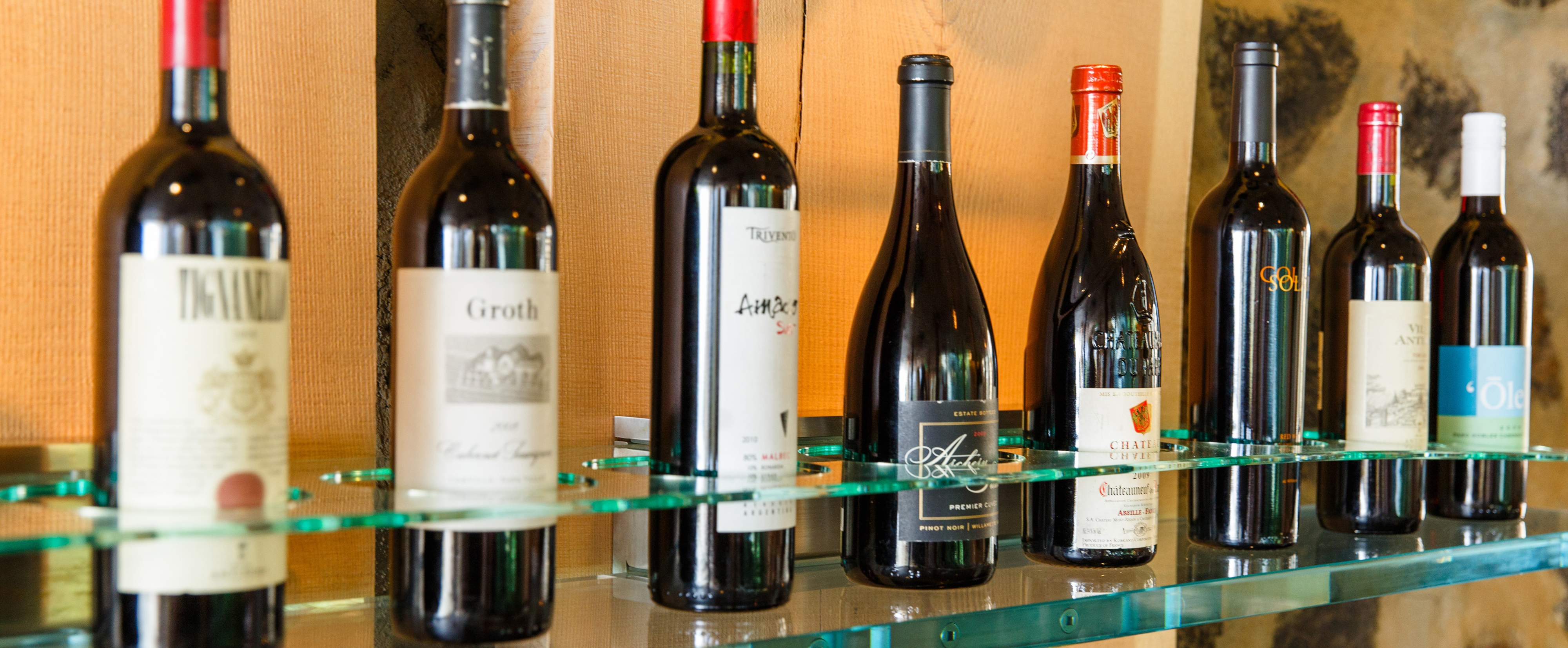 Eight bottles of red wine on a glass shelf with round slots