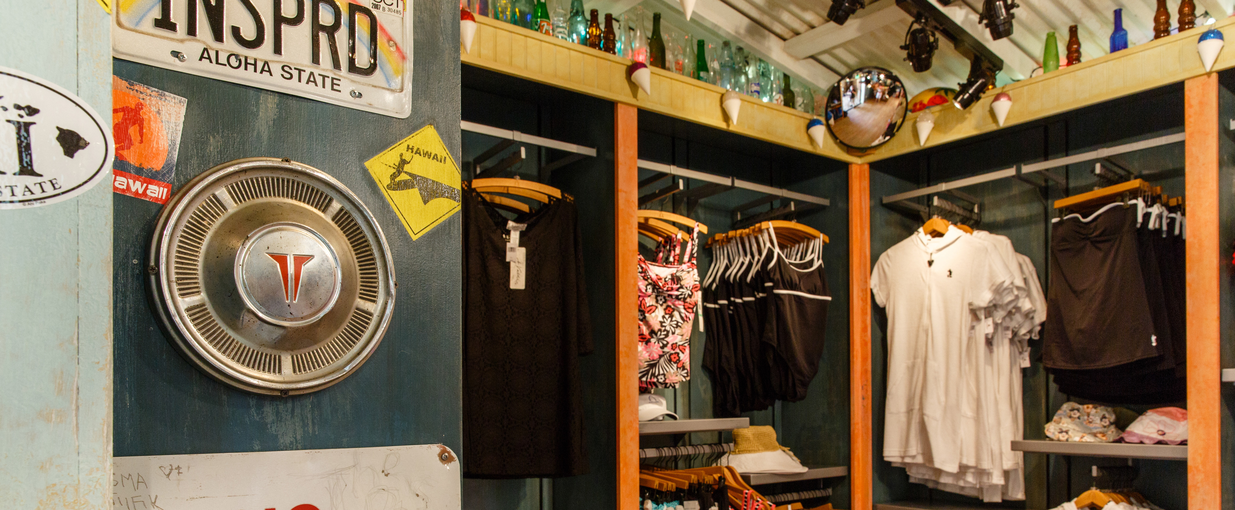 A hubcap and Hawaii memorabilia decorate a wall near hanging displays of swim and beach wear