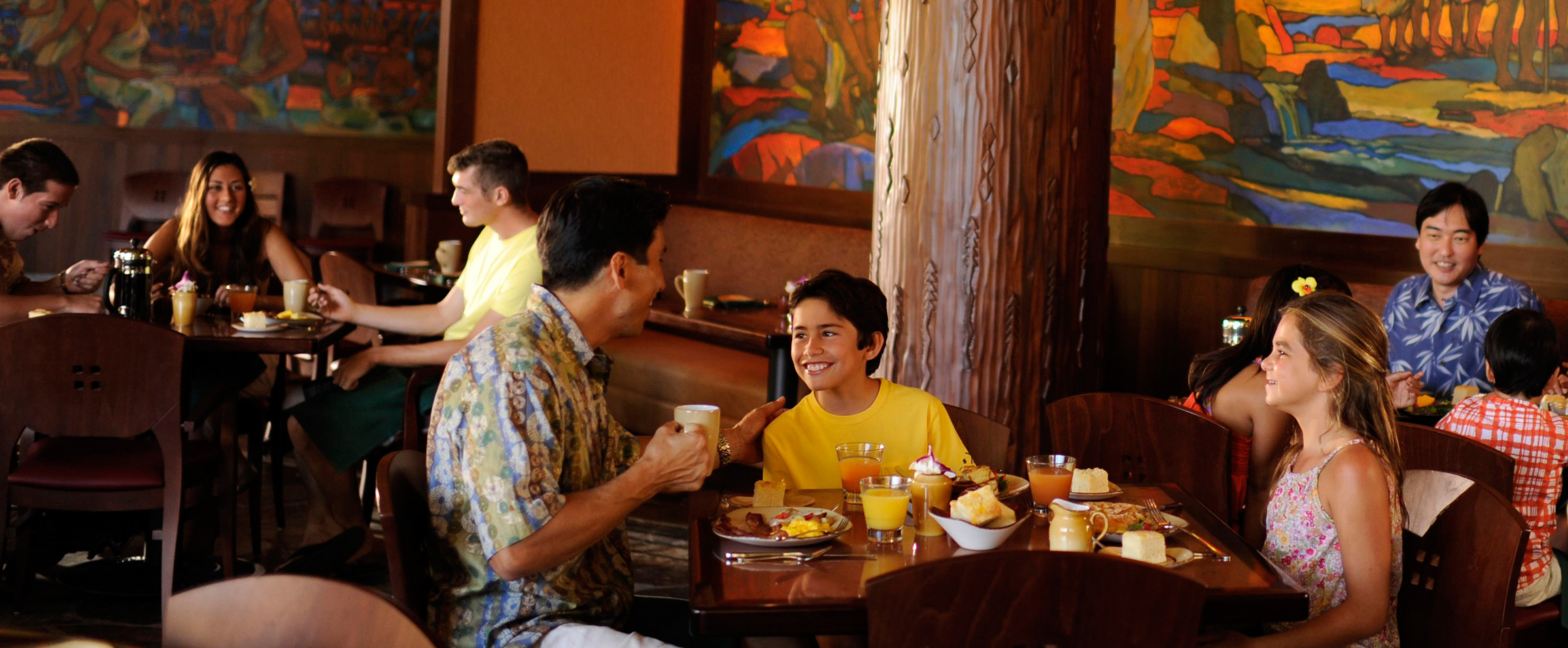 A father and son in an animated conversation at breakfast while a young daughter looks on