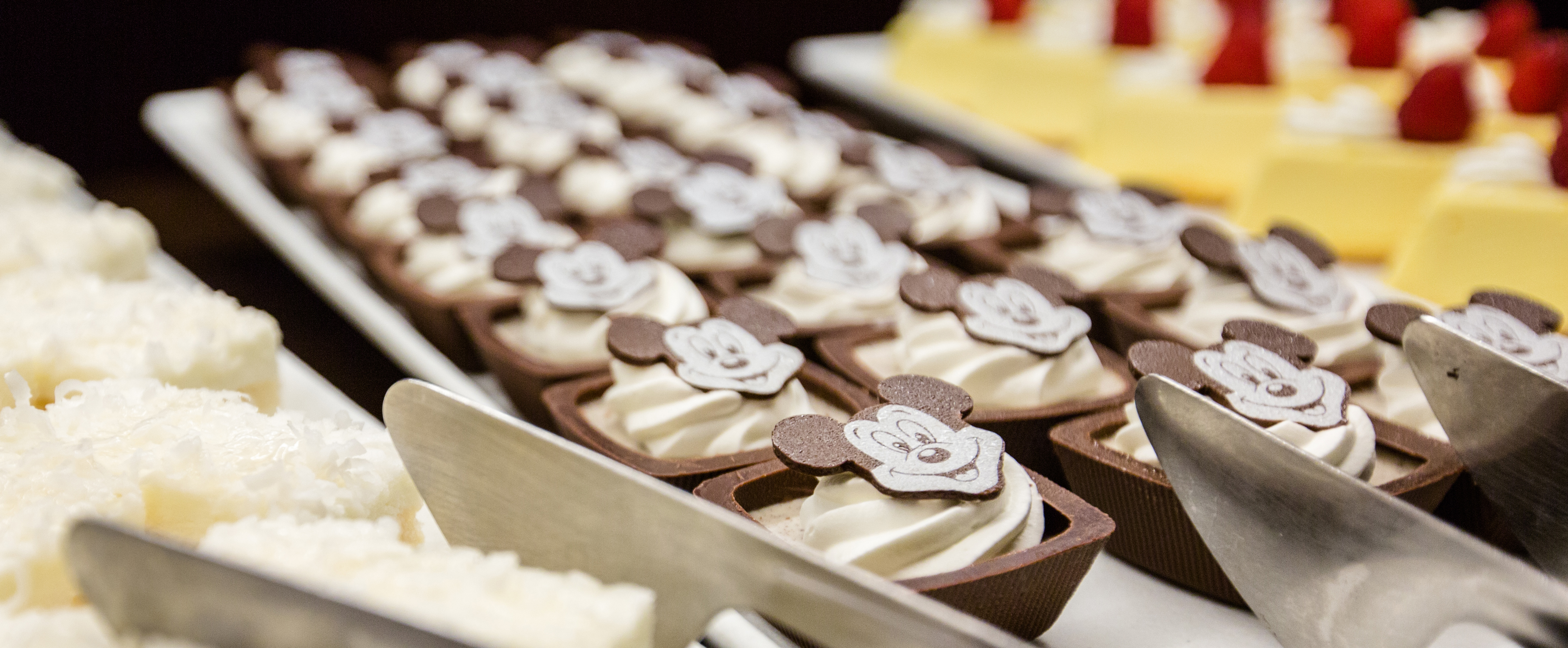 Chocolate Mickey faces decorate rows of square chocolate shells filled with white cream