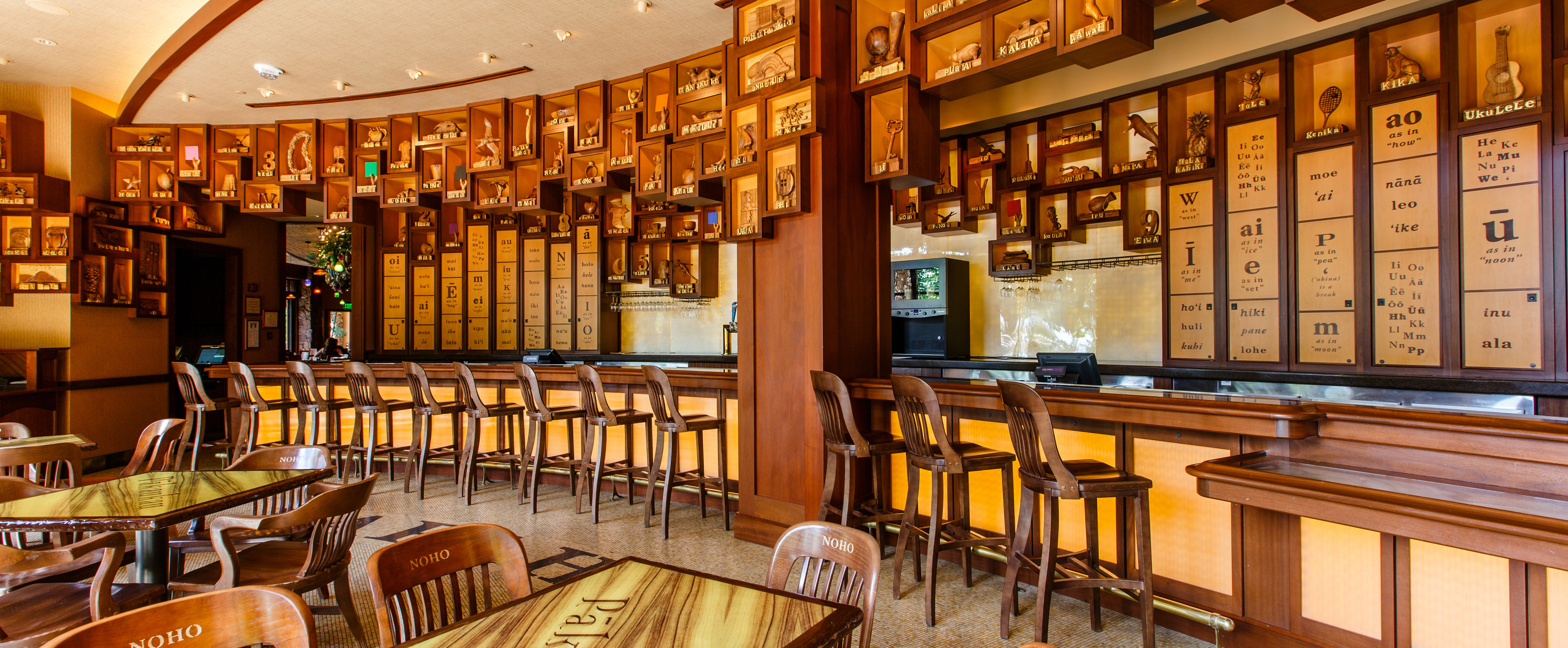 A long wood bar lined with chairs and wooden plaques featuring carved objects with Hawaiian words