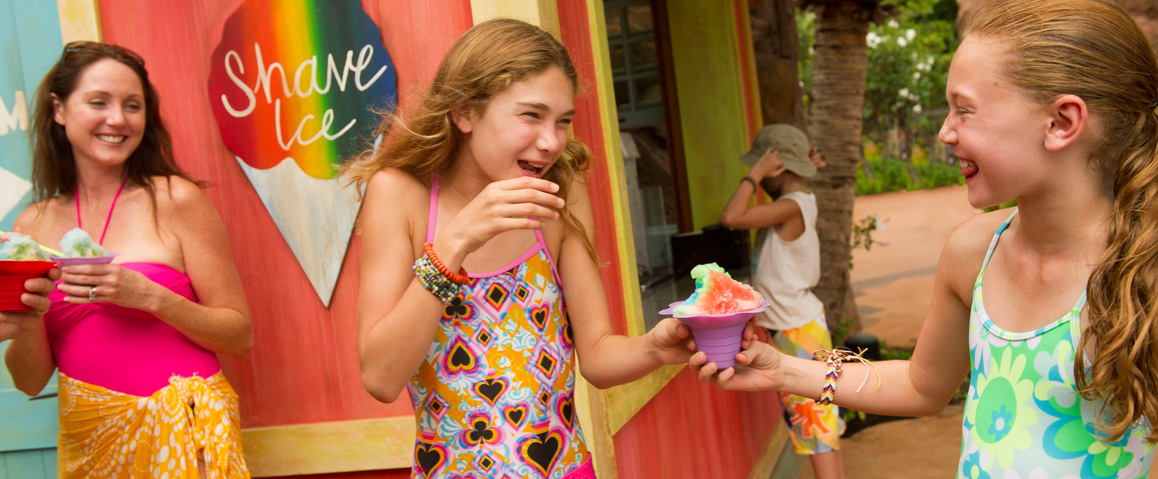 Two tween girls in swimwear laugh while clutching a shave ice dessert as a woman holding a shave ice looks on