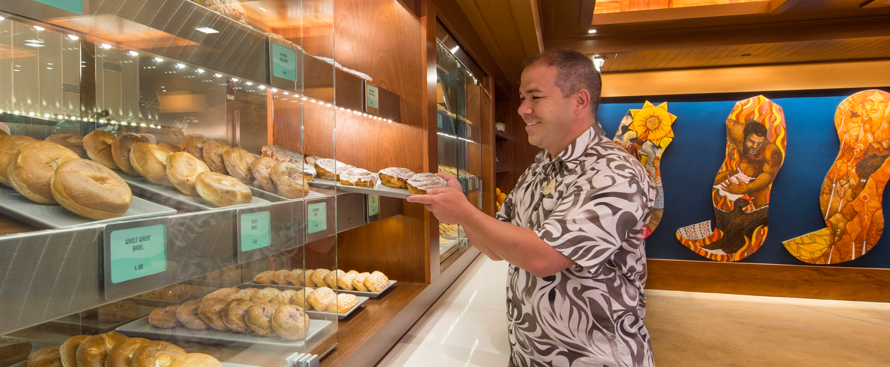 A Cast Member slides a tray of cinnamon rolls into a pastry case filled with bagels at Ulu Café