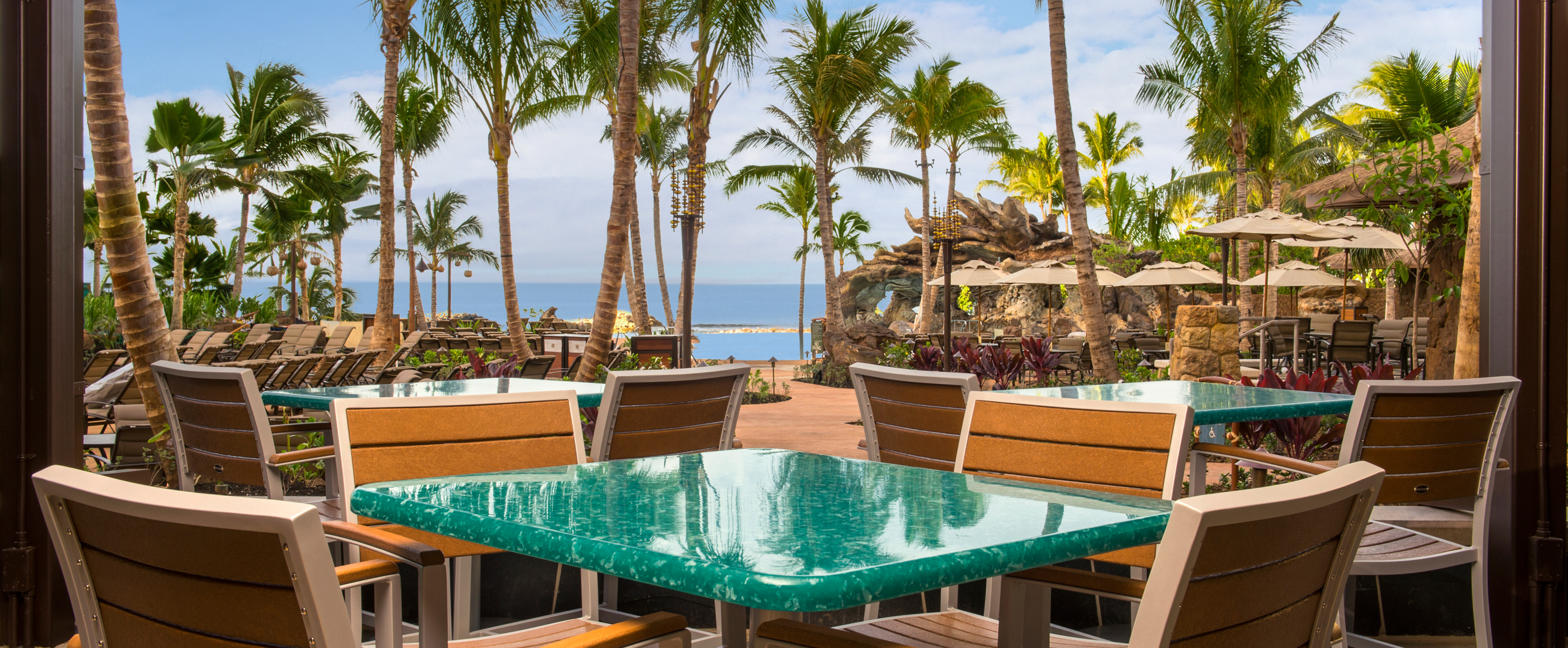 Outdoor tables on the covered patio look upon palm trees and an ocean view