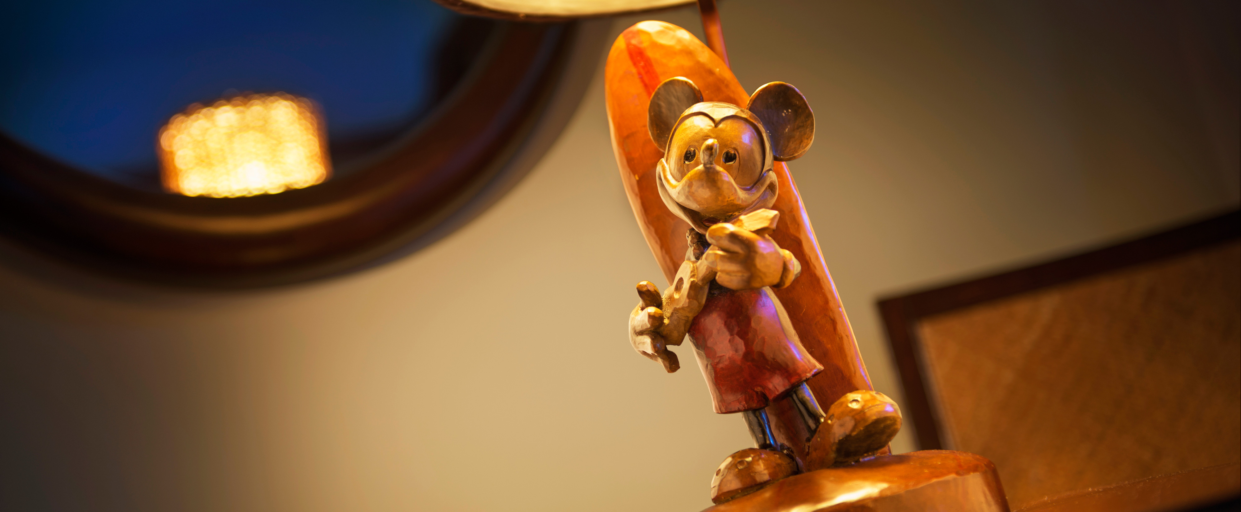 A wood-carved detail of Mickey with a ukulele and surfboard on the base of a lamp