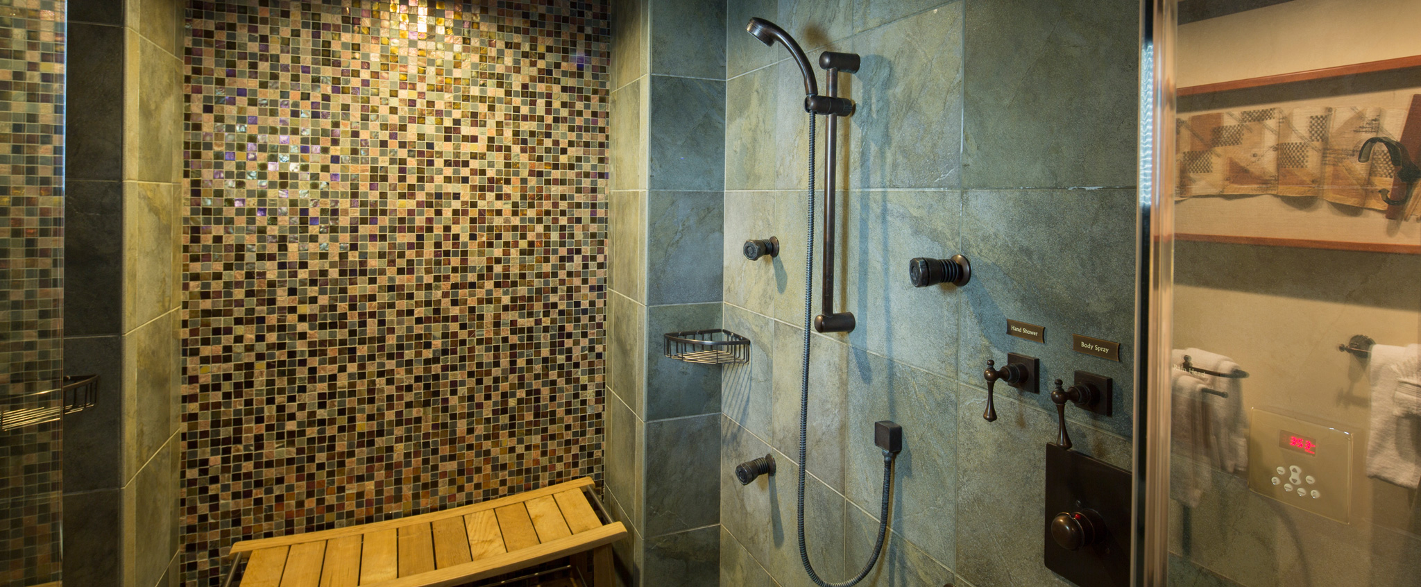 A large walk-in tiled shower has dark bronze fixtures and a wooden shower bench