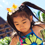 ケイキ・カバー・スプラッシュ・ゾーンで、母親と手をつなぎながら噴き上がるウォータジェットを飛び越えて遊ぶ小さな女の子と、背後で遊ぶ 5 人の子供たち
