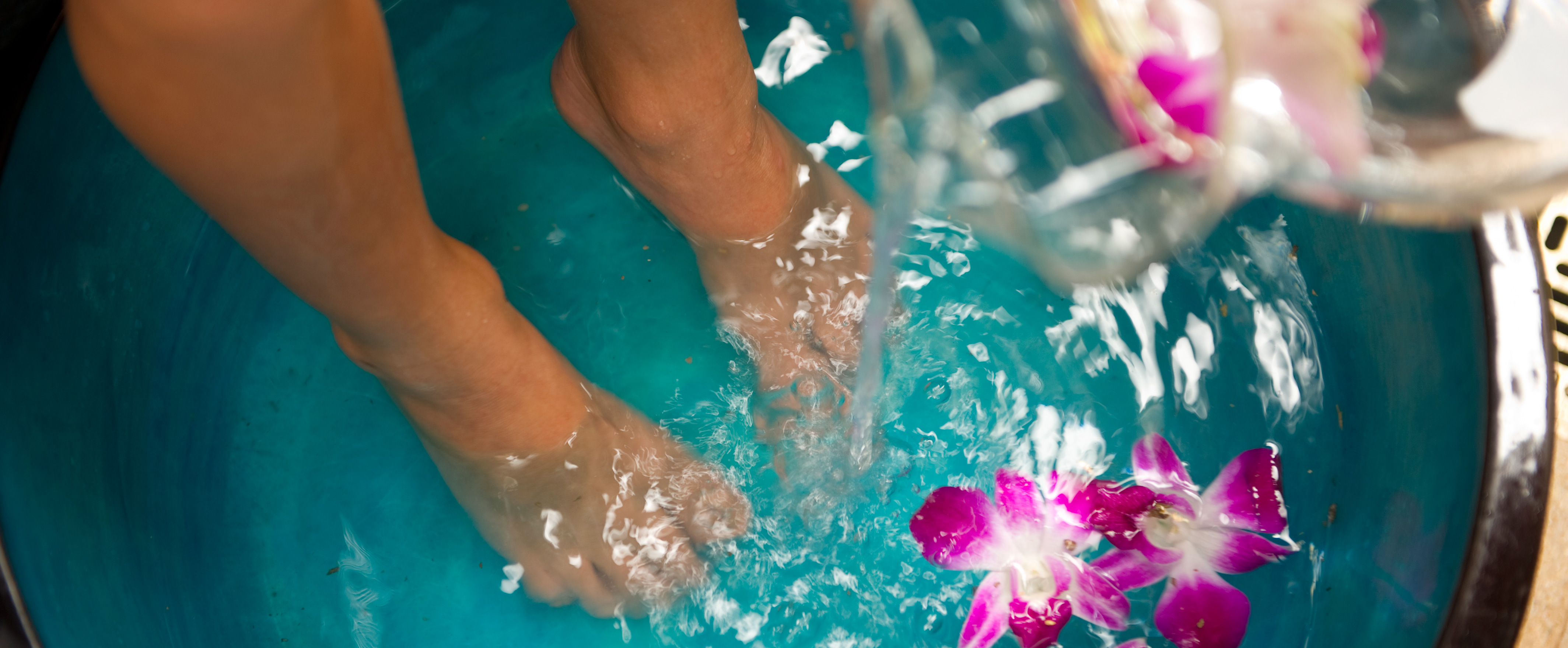 Feet in a large water-filled basin with floating fuchsia orchids as more water pours in